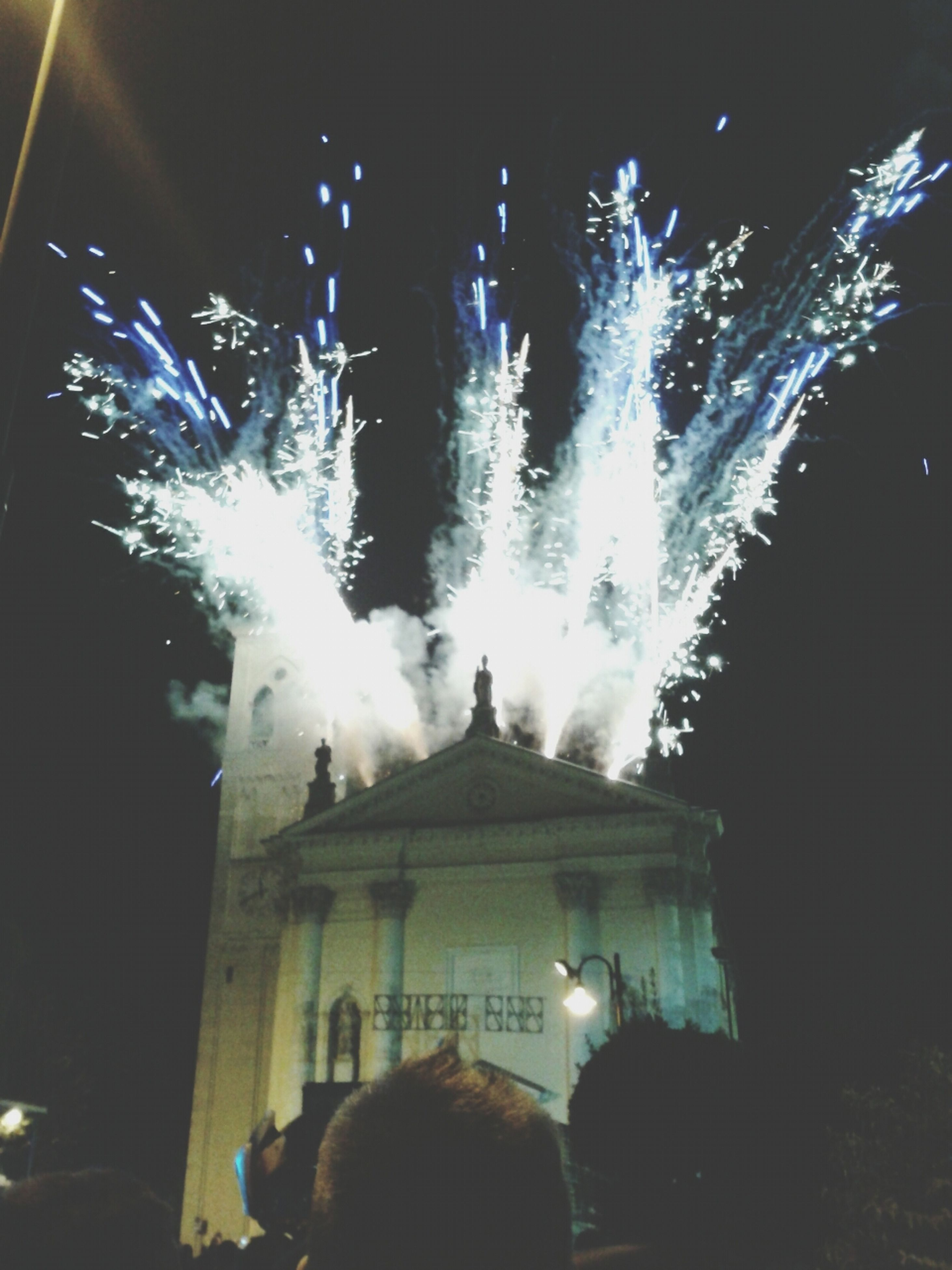 illuminated, night, lighting equipment, low angle view, built structure, glowing, architecture, building exterior, celebration, light - natural phenomenon, arts culture and entertainment, dark, firework display, firework - man made object, light, sky, electric light, event, outdoors, exploding