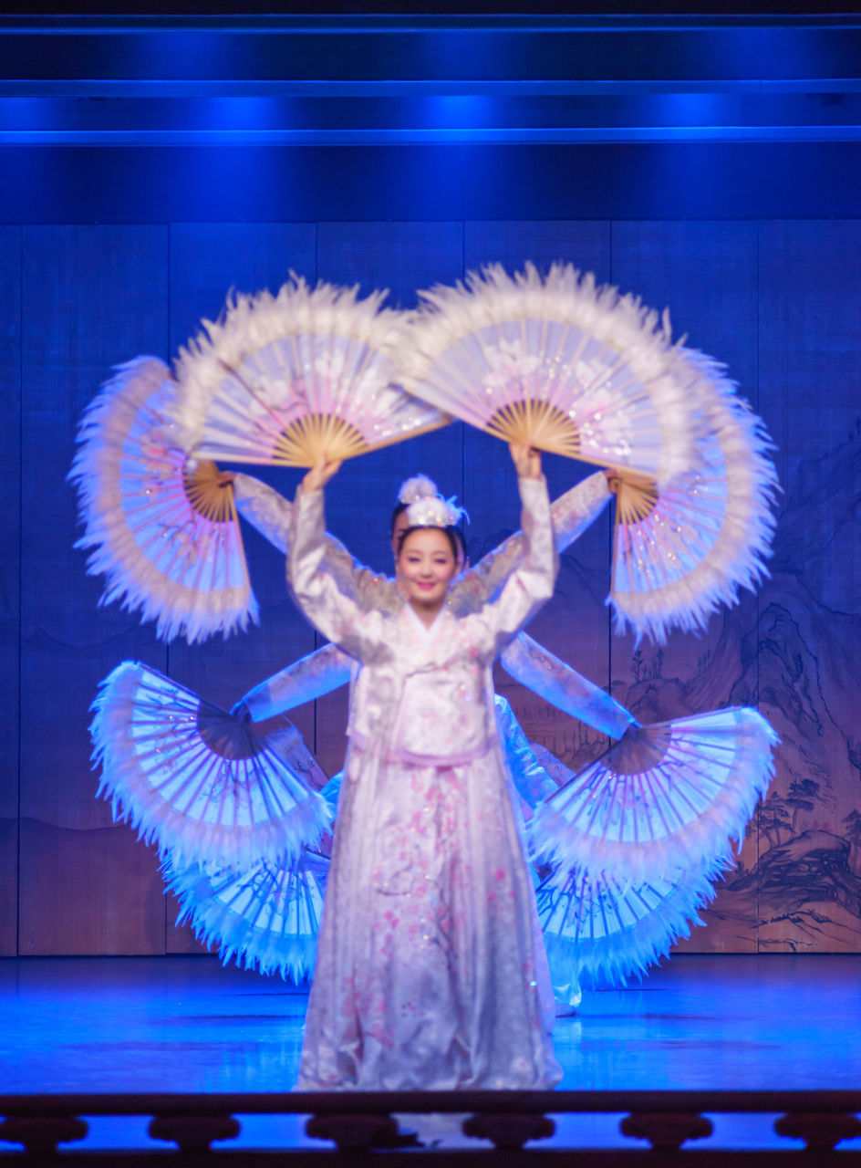 arms raised, human arm, performance, skill, arms outstretched, dancing, dancer, one person, performing arts event, looking at camera, human body part, front view, arts culture and entertainment, portrait, smiling, happiness, indoors, stage - performance space, stage costume, young adult, people, one woman only, ballet dancer, adult, one young woman only, adults only, day