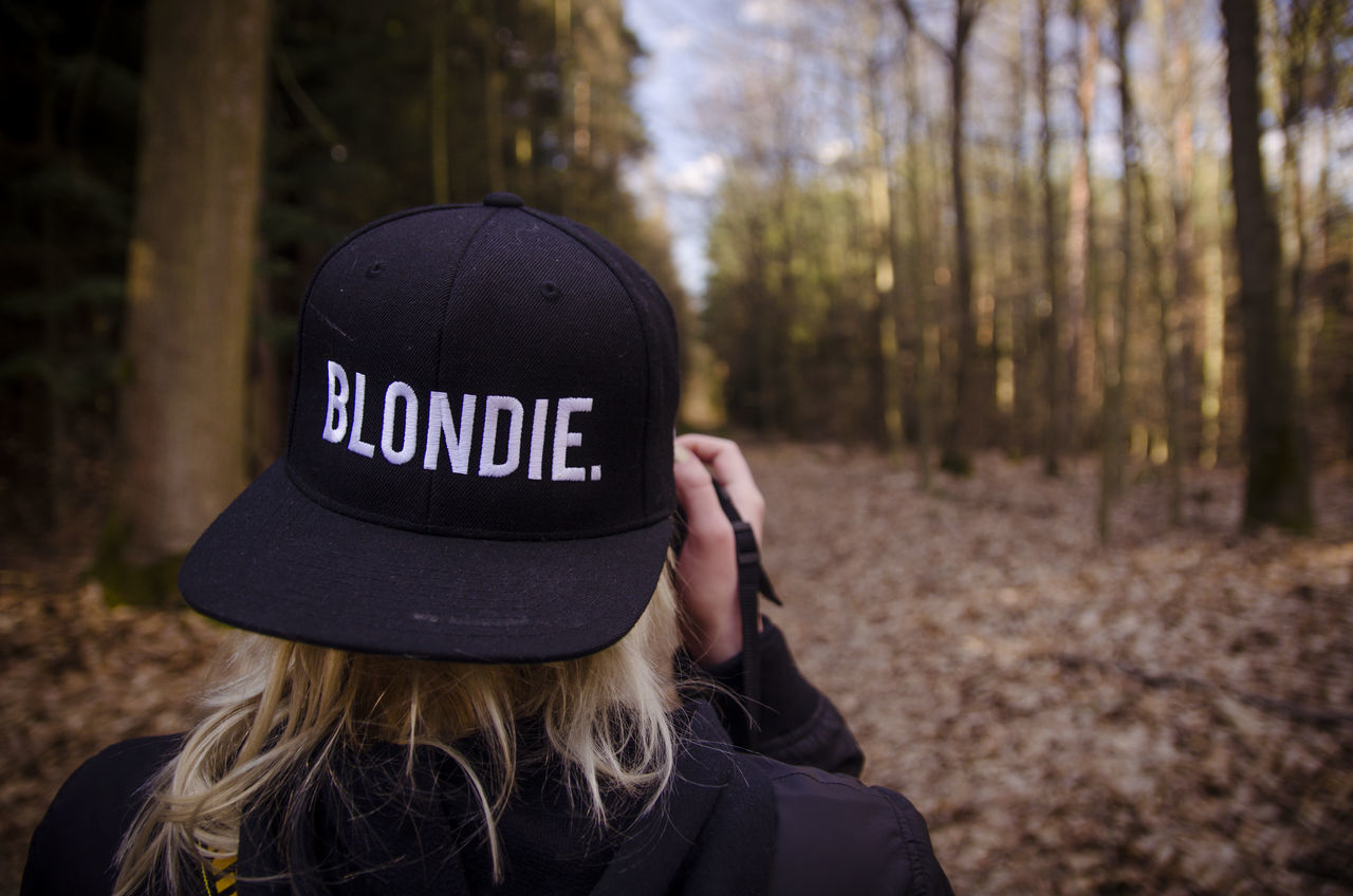 text, real people, tree, communication, forest, focus on foreground, one person, cap, headshot, day, outdoors, lifestyles, women, close-up, human hand, people