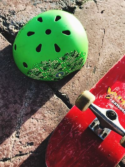 Skaters life Streetphotography Childhood Outdoors Objects Close-up Green Color Red High Angle View Different Perspective Ground Wheels Skateboard Safety Helmet Hobbies Not In Use Fun Shapes Text Metal