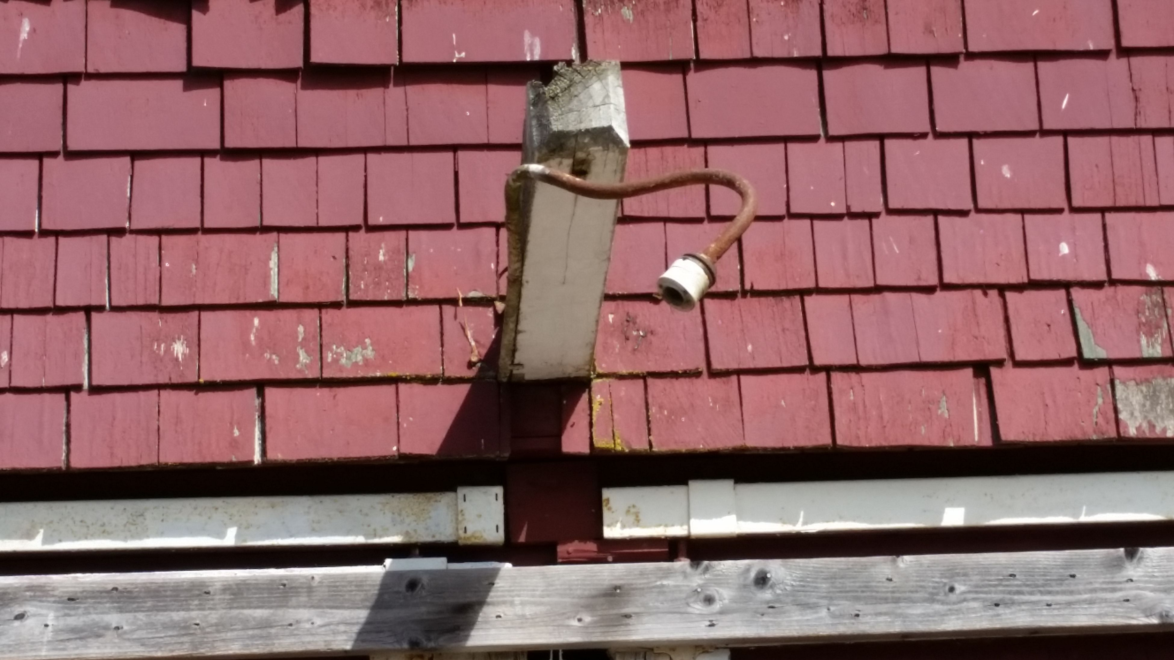Old Light Fixture On Red Barn. Red Shingles, Antique Light/lamp On Red Building. Abandoned Building. Arural.Rustic.