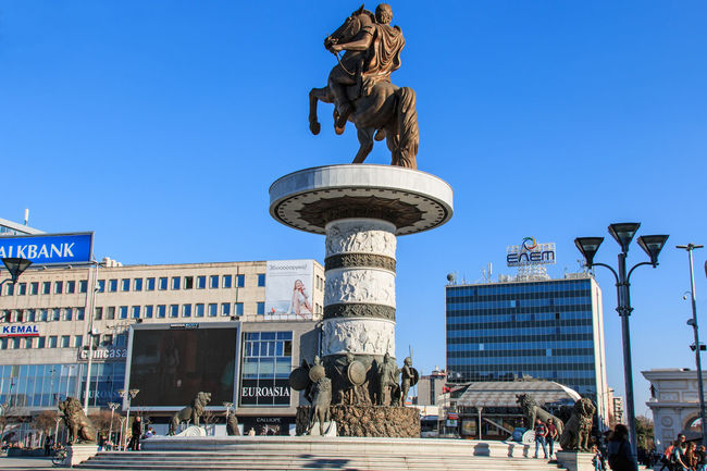 Monument of Alexander The Great in Skopje's main square with people passing by. Architecture Balkans Blue Building Exterior Built Structure City City Life Clear Sky Day Development East Europe Macedonia Memories Monument Outdoors Skopje Skyscraper Tall Tall - High Tourism Tourist Tower Travel Destinations Vacations