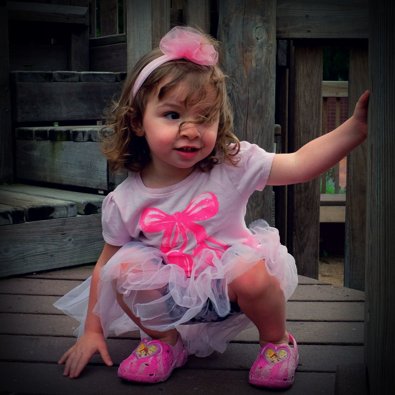 Little girl squatting outdoors