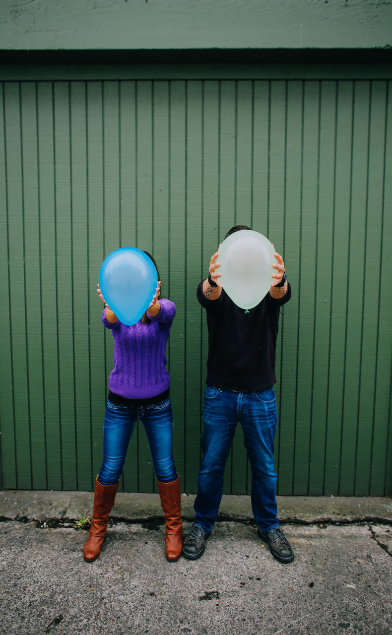 Man And Woman Covering Face With Balloons While Standing Against Wall