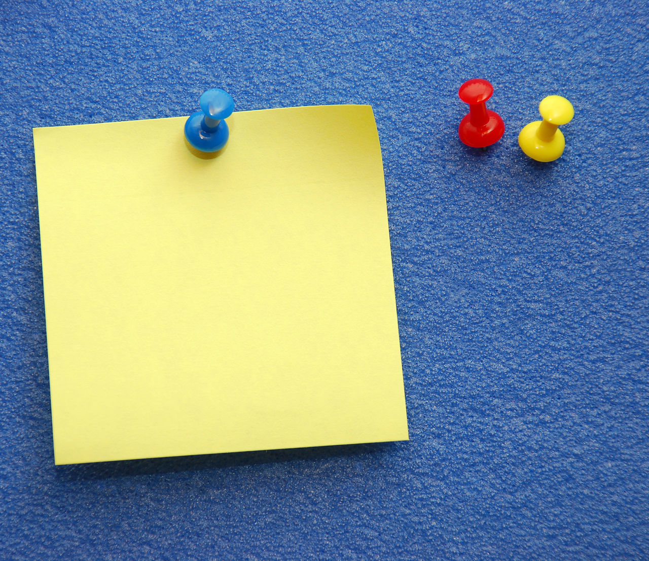 A yellow notepaper pinned on a blue board plus red and yellow extra pins at the side. Adhesive Note Attached Blank Bulletin Board Bulletin Board Bulletinboard Chores Close-up Communication Copy Space Day Indoors  Message No People Note Notepaper Notify Reminder Reminders Removable Small Group Of Objects Sticky Sticky Notes Thumbtack Yellow