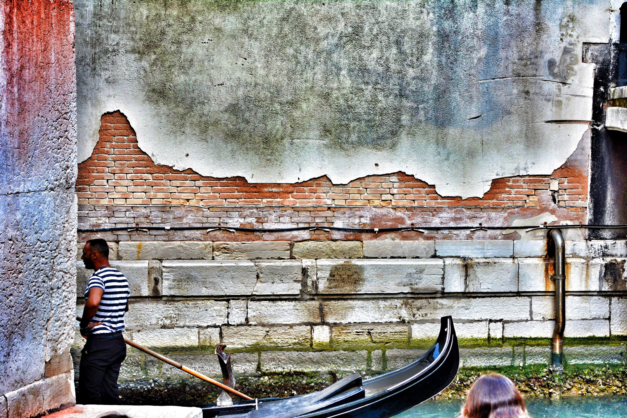 wall - building feature, brick wall, shoe, outdoors, casual clothing, day, weathered, sky