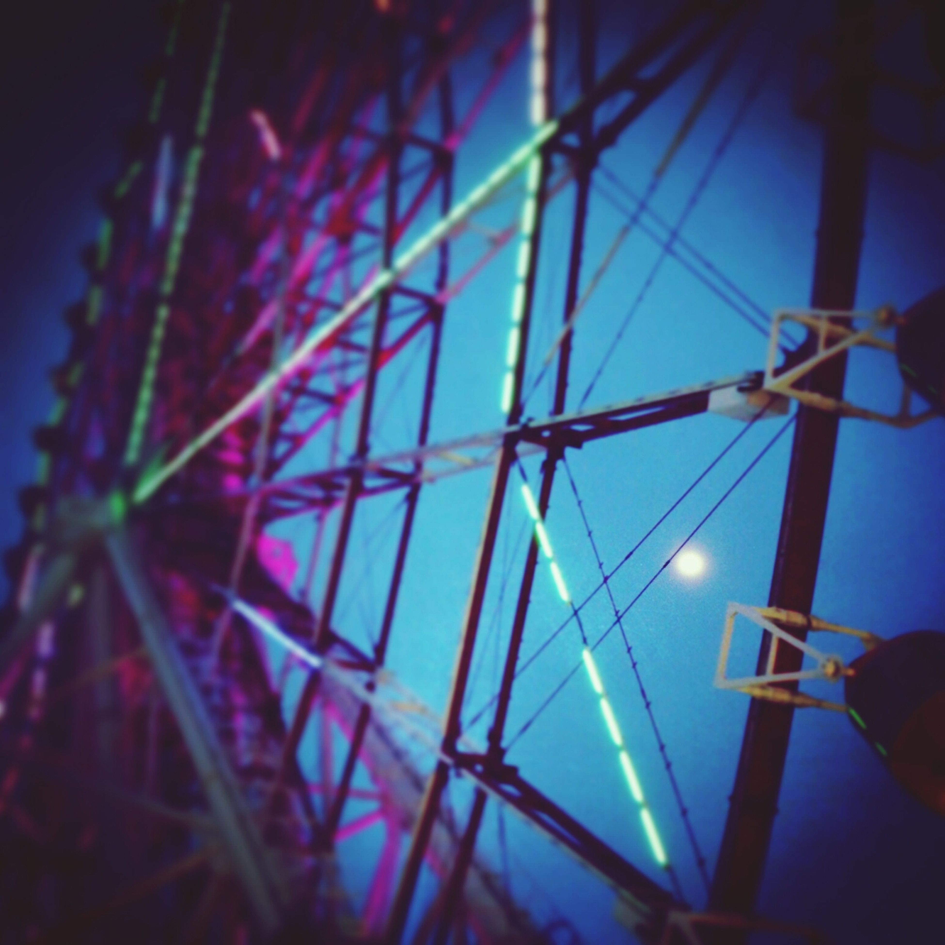 low angle view, illuminated, night, metal, silhouette, arts culture and entertainment, sky, indoors, blue, lighting equipment, dusk, close-up, part of, no people, built structure, cropped, metallic, clear sky, pattern