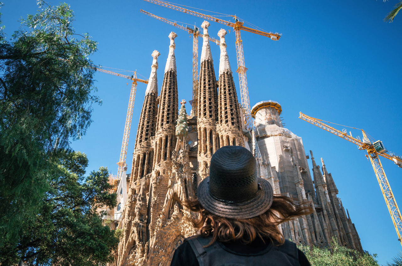 Young woman traveler in a hat looks at the Sagrada Familia the most famous tourist attraction of Barcelona, Catalonia Spain Adult Adventure Architecture Architecture_collection Barcelona Built Structure Catalonia Hat Landmark Looking Into The Future Outdoors Place Of Worship Sagrada Familia SPAIN Tourism Tourist Travel Travel Destinations Traveler Vacations Woman