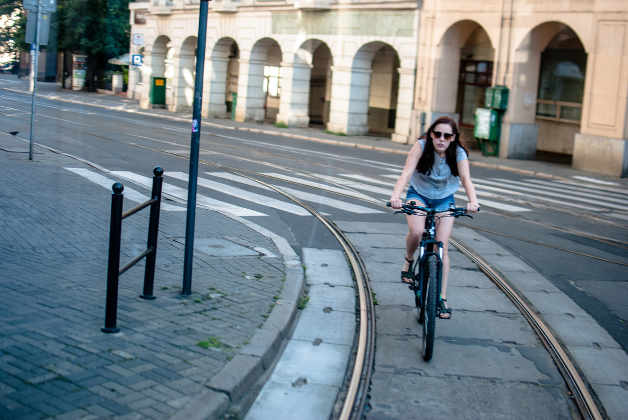 bicycle, real people, one person, full length, lifestyles, transportation, cycling, teenager, happiness, mode of transport, street, young adult, casual clothing, smiling, outdoors, riding, built structure, city, architecture, day, building exterior, young women, people, adult, adults only