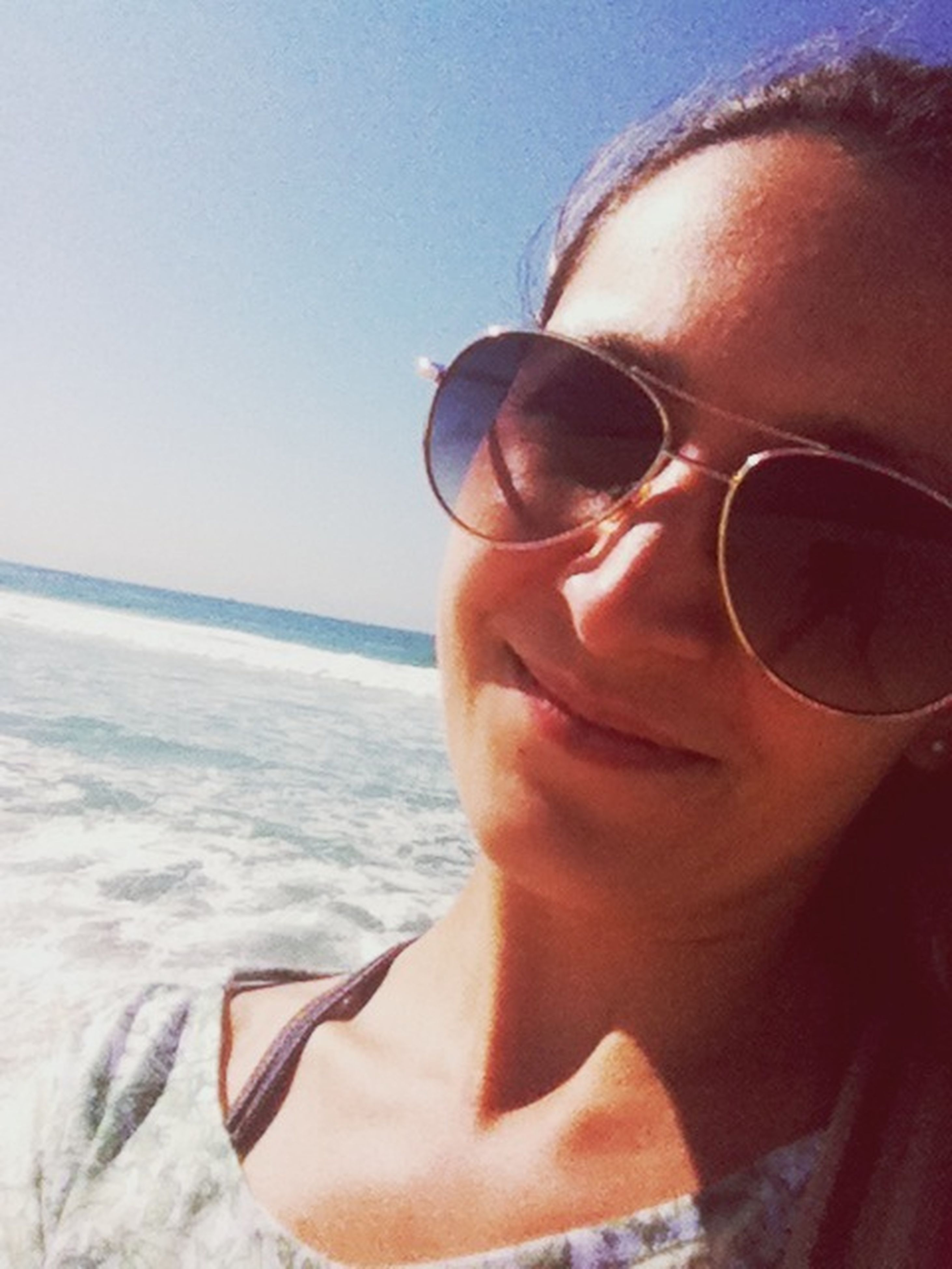sunglasses, young adult, person, lifestyles, leisure activity, headshot, portrait, sea, looking at camera, beach, water, young women, sunlight, head and shoulders, front view, sky, vacations