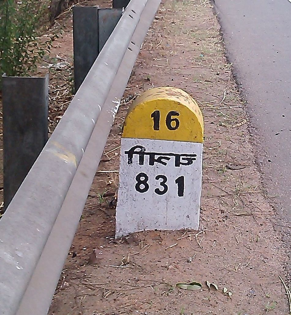 A milestone with information written in flip manner ..name of the place is a mirror image of the text !! Careless Ignorance Information Sign Irresponisble Milestone Mistake Negligence Not My Job Wrong