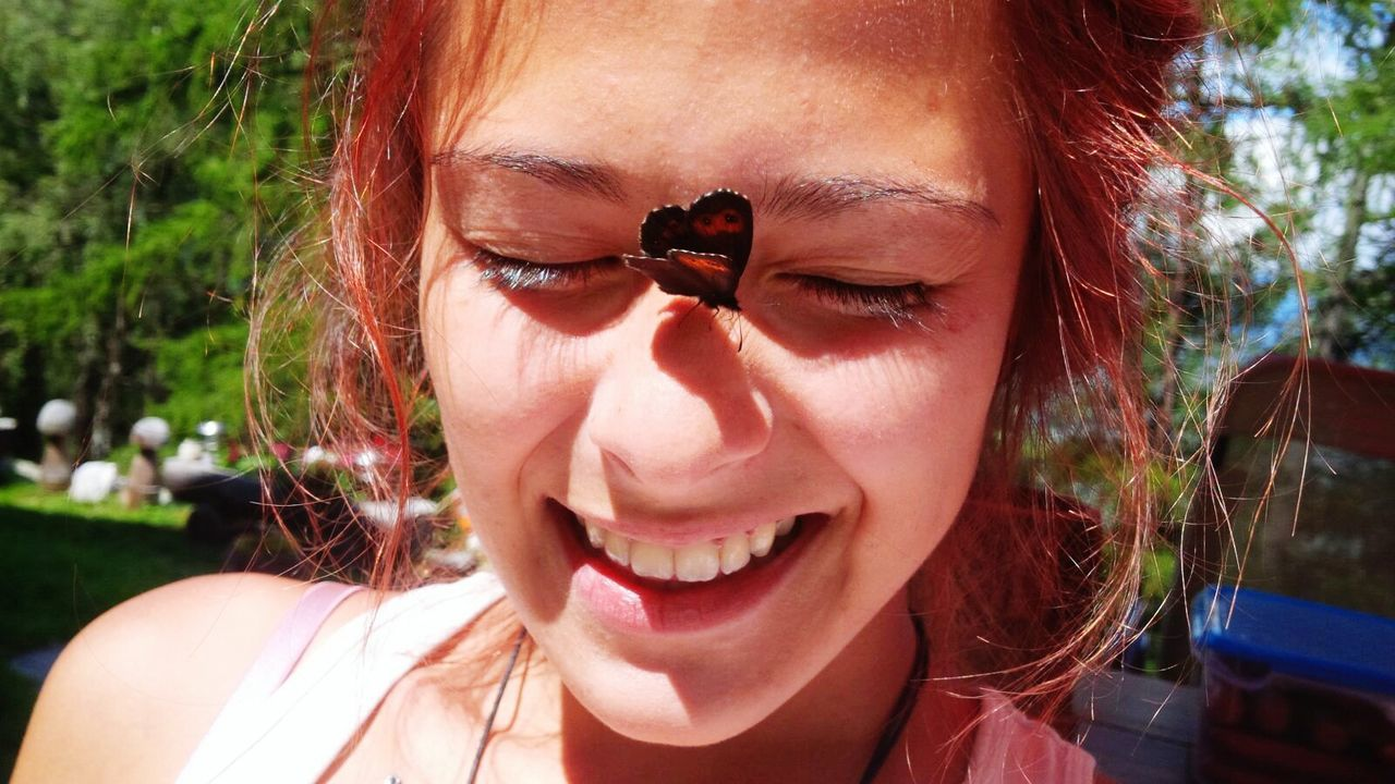 Close-Up Of Smiling Young Woman With Butterfly On Sunny Day