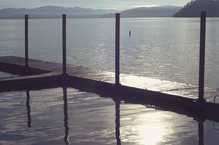 Early morning walk on the dock My Year My View Nature's Diversities Idyllic Lake Lake County, Ca Monochrome Morning Sky Mountain Nature Nature Outdoors Pier Railing Reflection Rippled Scenics Sea Sky Sunset Tranquil Scene Tranquility Travel Destinations Traveling Water Wood - Material