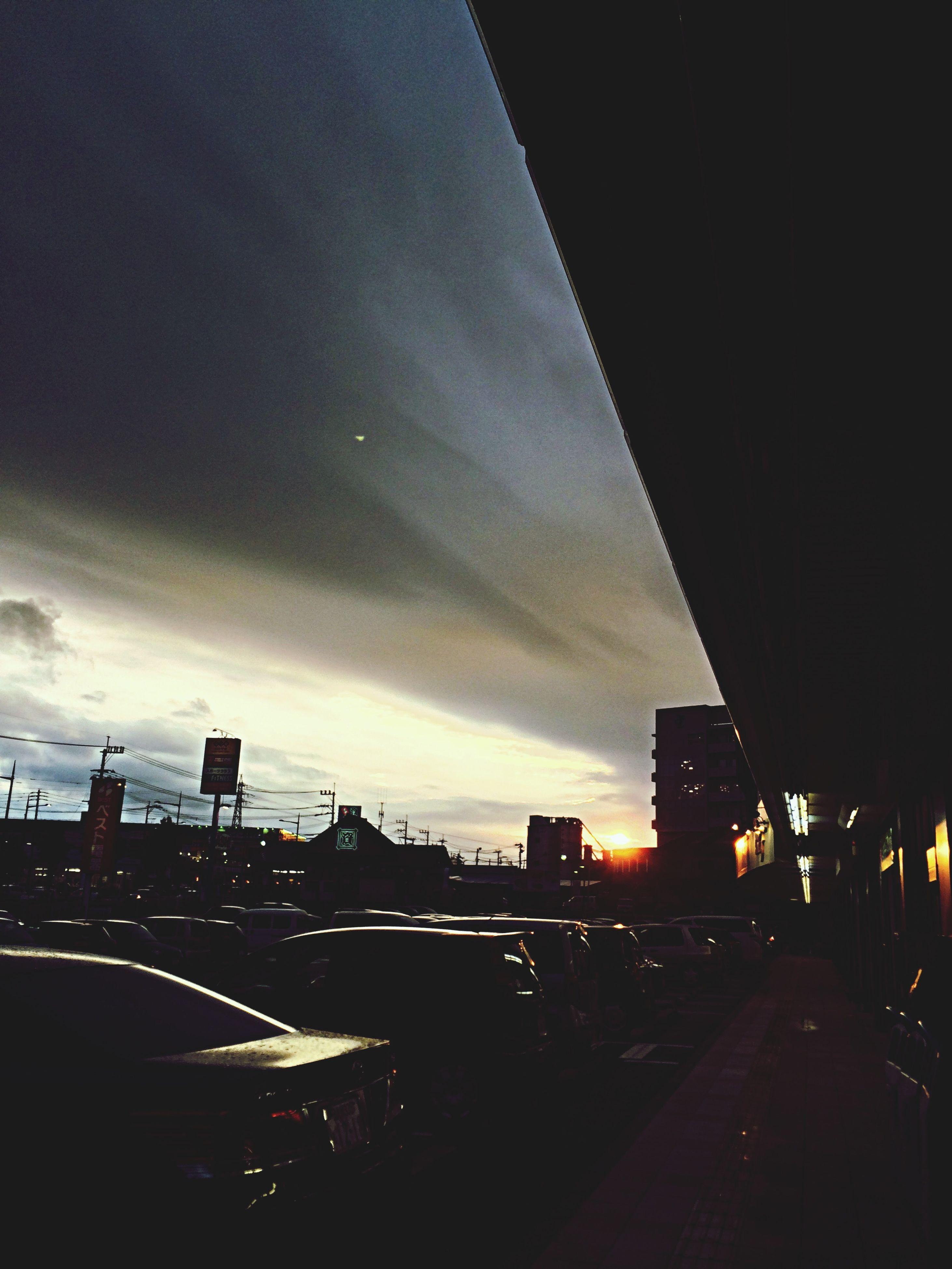 architecture, building exterior, built structure, sky, city, sunset, illuminated, transportation, cloud - sky, road, car, dusk, street, silhouette, city life, cityscape, night, land vehicle, street light, outdoors