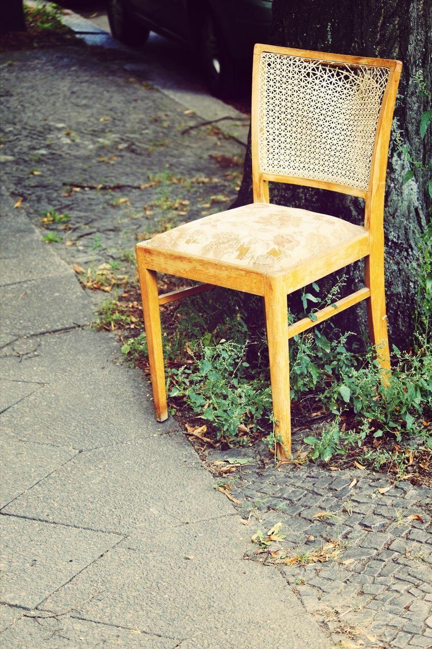 Abandoned yellow chair on sidewalk