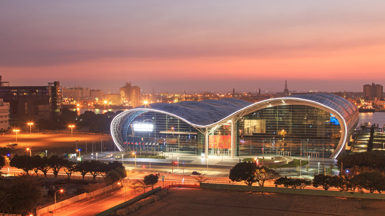 Kaohsiung, Taiwan - February 26,2015: Sunset over the newly opened Kaohsiung Exhibition Center. Architecture ASIA Building 85 Built Structure City City Life Cityscape Cloud - Sky Dusk Exibition Hall Green Library Iconic Buildings Illuminated Kaohsiung Kaohsiung Exibition Center Kaohsiung, Taiwan Light Trail Modern Buildings Night No People Orange Color Outdoors Sky Sunset Taiwan