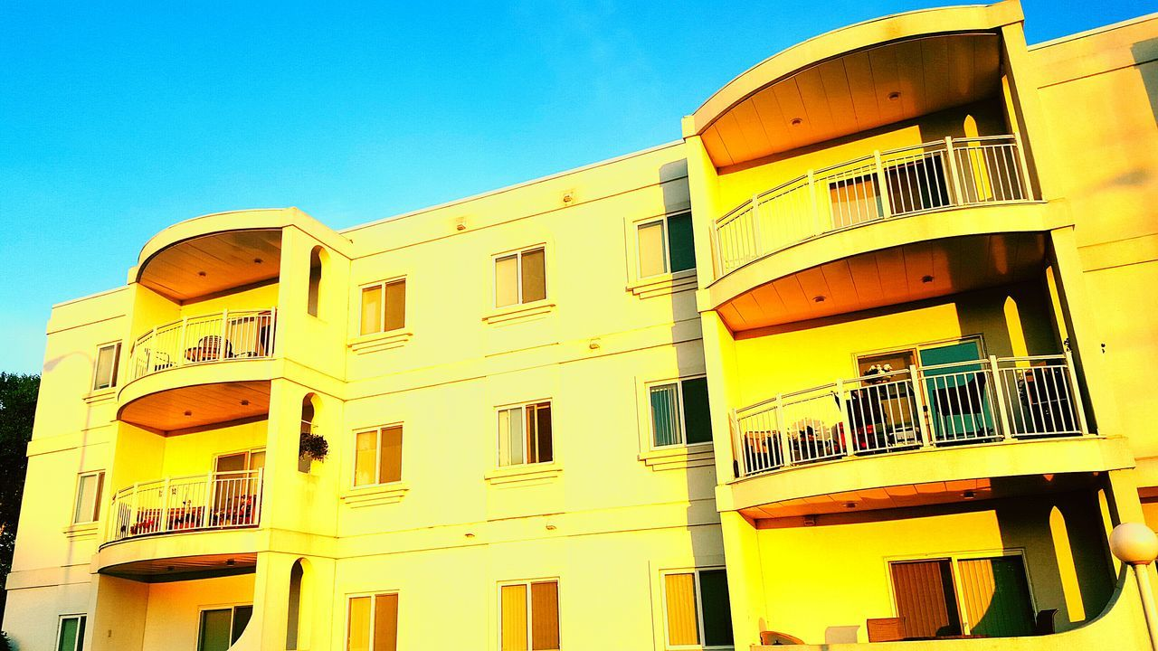 architecture, building exterior, built structure, window, yellow, balcony, low angle view, no people, sky, residential building, day, sunlight, outdoors, clear sky, blue, apartment, city