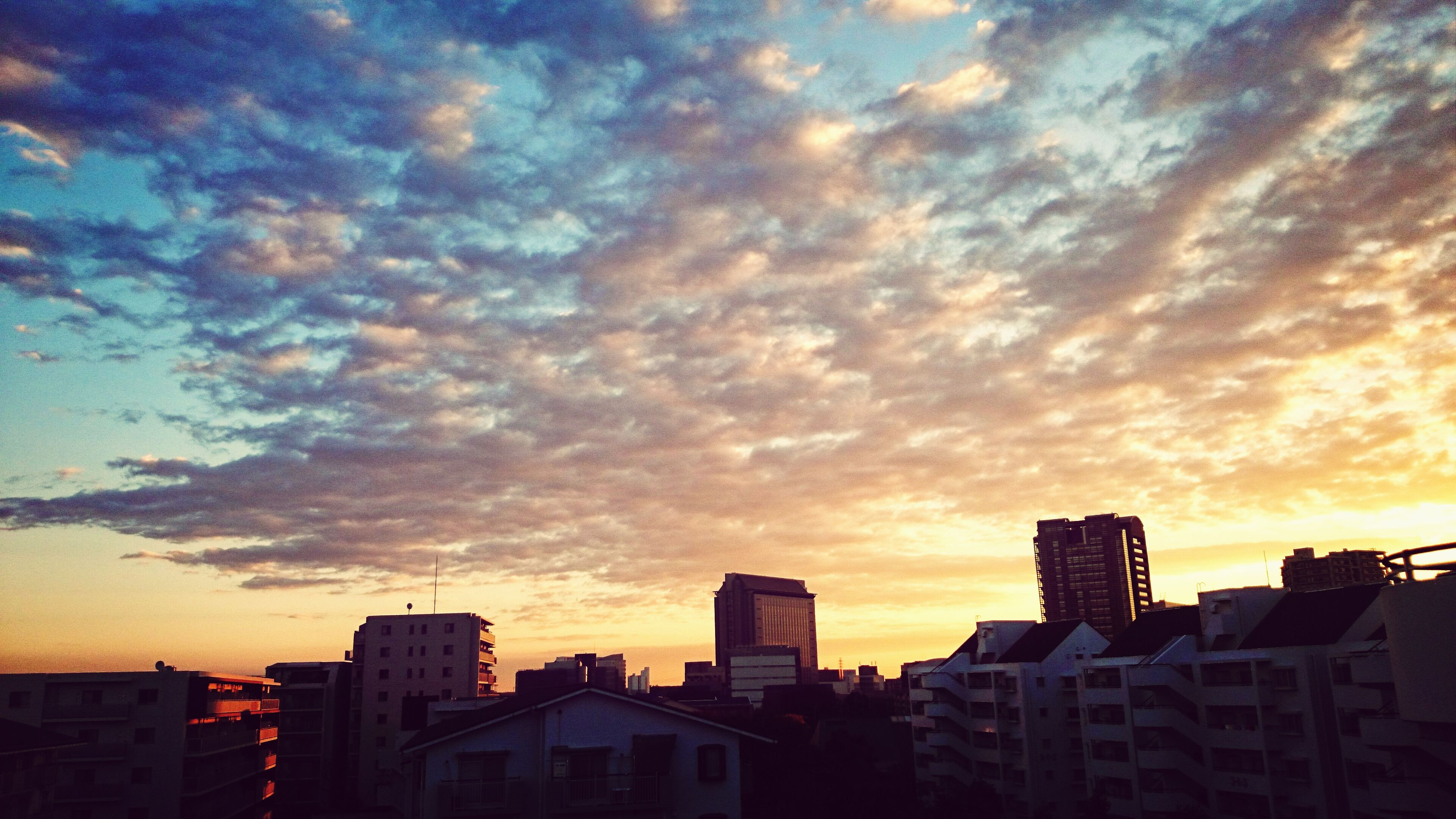 sunset, building exterior, architecture, built structure, sky, orange color, cloud - sky, city, silhouette, cloudy, dramatic sky, residential structure, residential building, cityscape, building, cloud, weather, residential district, house, outdoors