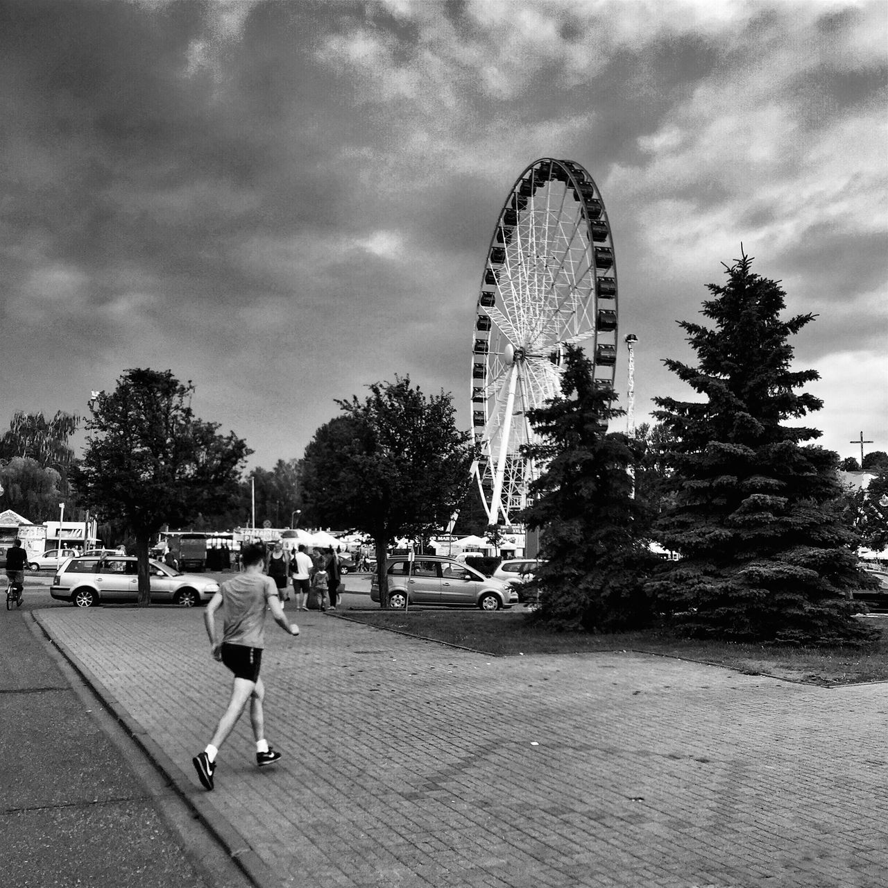 tree, full length, leisure activity, cloud - sky, outdoors, ferris wheel, sky, rear view, city life, building exterior, built structure, arts culture and entertainment, real people, architecture, amusement park, day, men, city, one person, adult, people