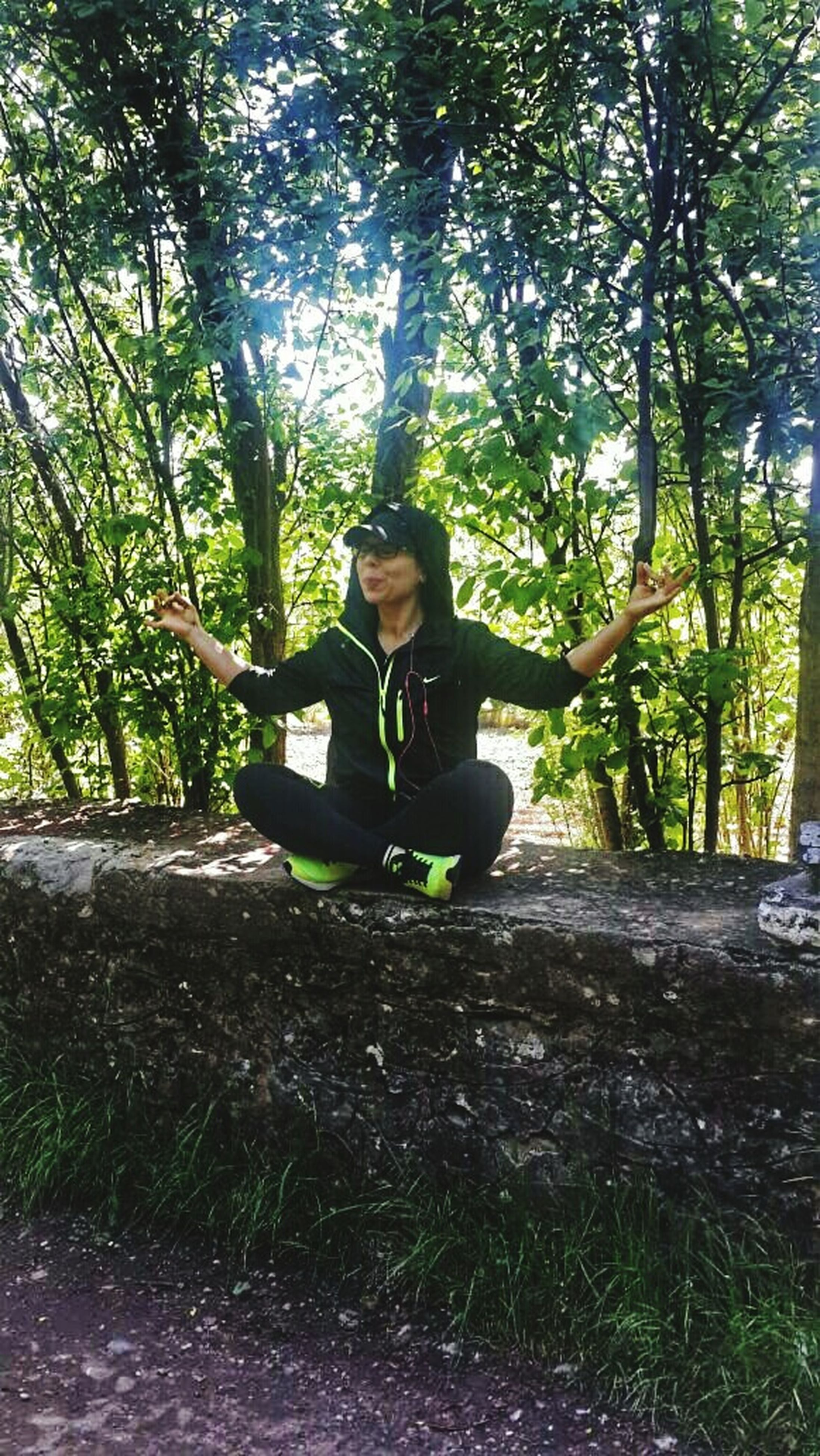tree, lifestyles, leisure activity, young adult, casual clothing, full length, person, sitting, young women, forest, smiling, looking at camera, portrait, relaxation, three quarter length, growth, nature