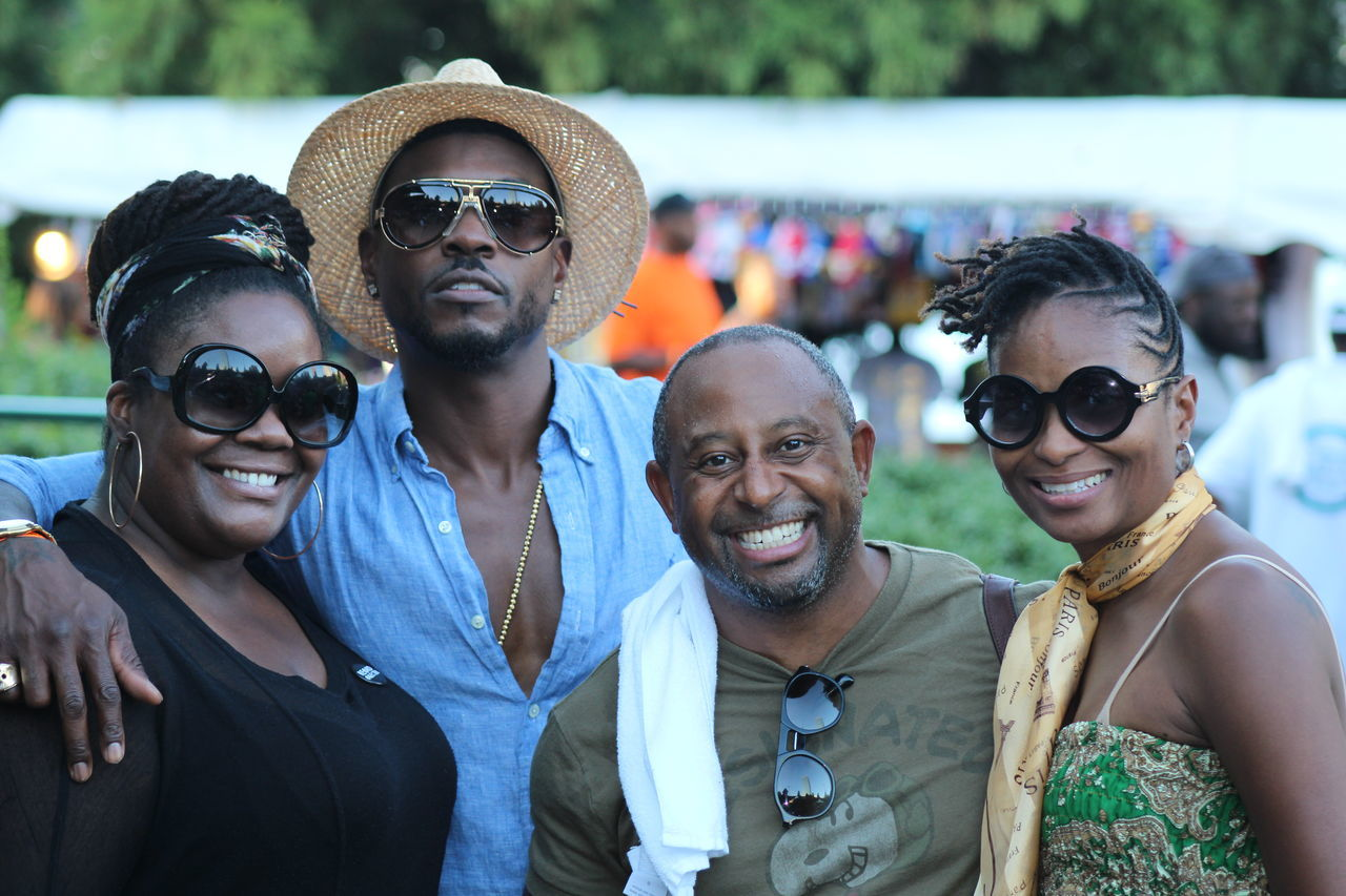 sunglasses, togetherness, smiling, real people, portrait, looking at camera, focus on foreground, young adult, leisure activity, young women, outdoors, day, mid adult men, standing, young men, lifestyles, fun, happiness, enjoyment, friendship, men, headshot, eyeglasses, cheerful, arm around, selfie, people