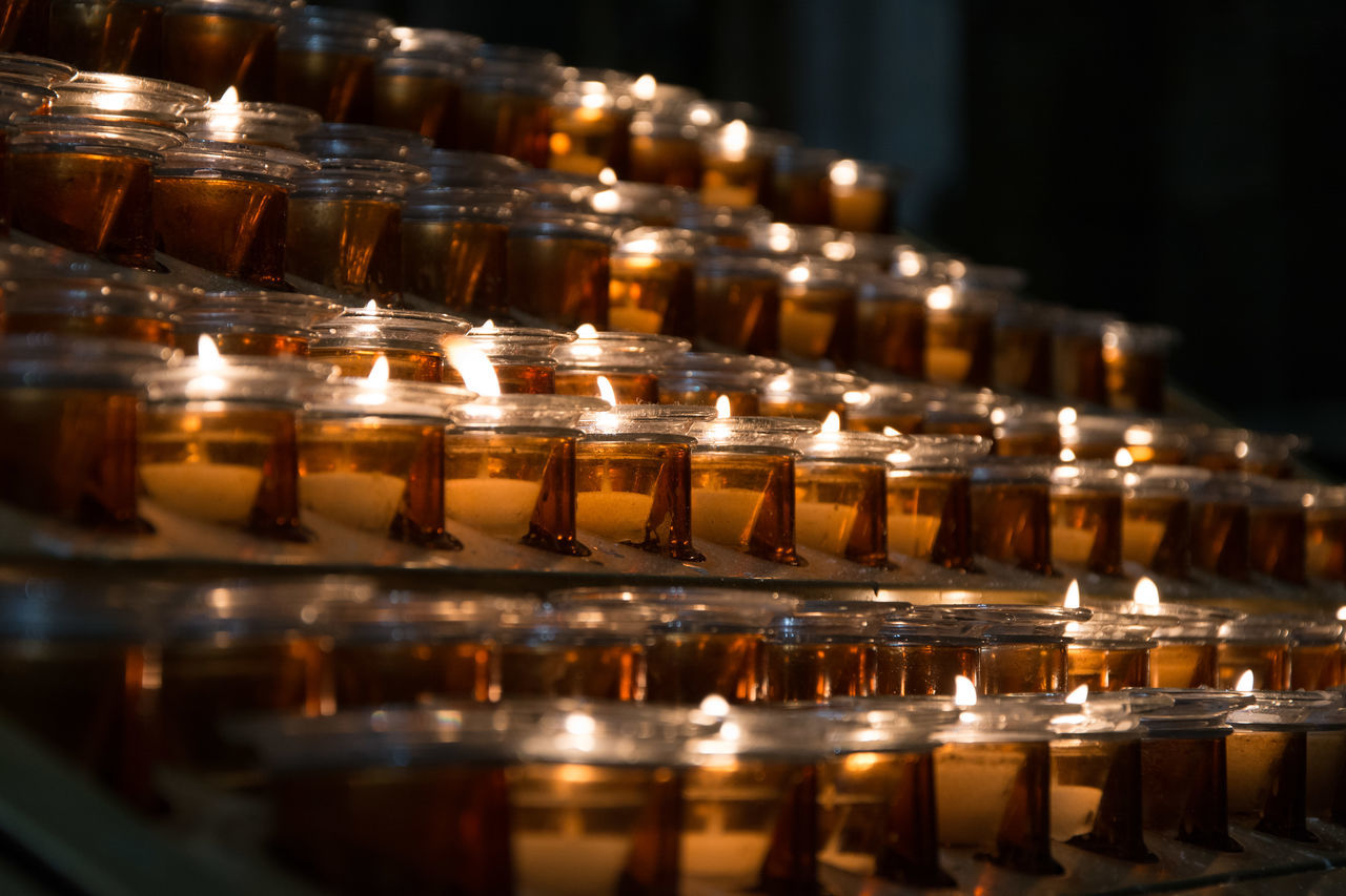 candle, flame, reflection, religion, burning, in a row, tea light, spirituality, place of worship, no people, illuminated, large group of objects, indoors, table, close-up, heat - temperature, day