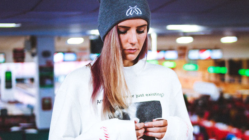Fashion High Resolution Adult Casual Clothing Close-up Communication Day Focus On Foreground Front View Game Room Holding Indoors  Lifestyles Majestic Casual Majesticcasual One Person People Real People Standing Text Thoughts Waist Up Wireless Technology Young Adult Young Women