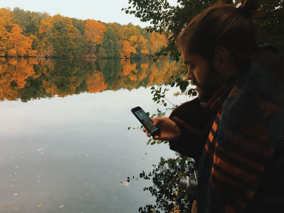 Nature Real People Tree Water Technology One Person Lifestyles Wireless Technology Smart Phone Young Adult Lake Leisure Activity Mobile Phone Day Outdoors Photography Themes Communication Portable Information Device Holding Beauty In Nature Autumn Autumn Colors