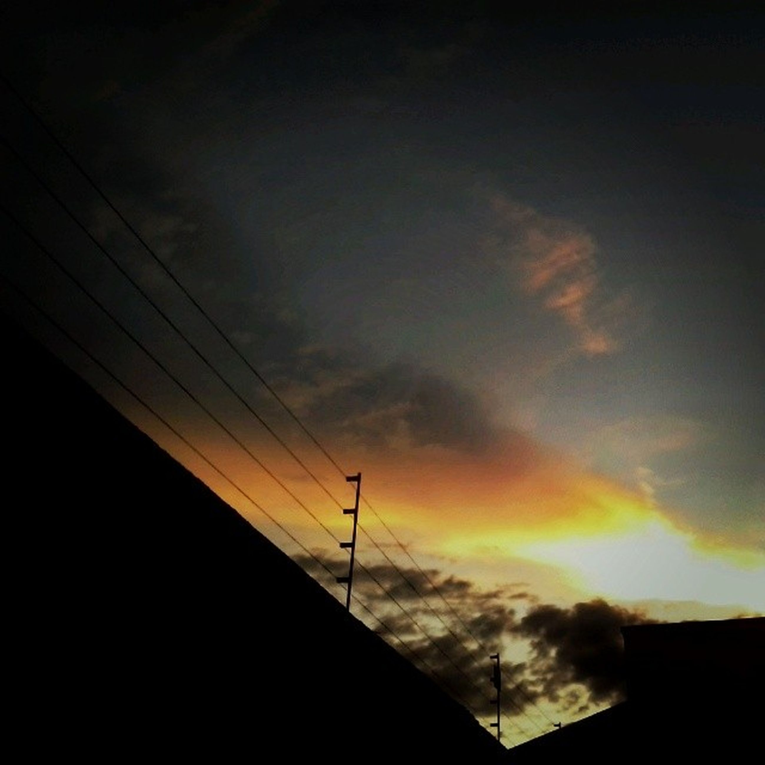 low angle view, sky, sunset, built structure, silhouette, architecture, cloud - sky, building exterior, cloudy, orange color, power line, dusk, cloud, high section, electricity, outdoors, nature, no people, scenics, connection