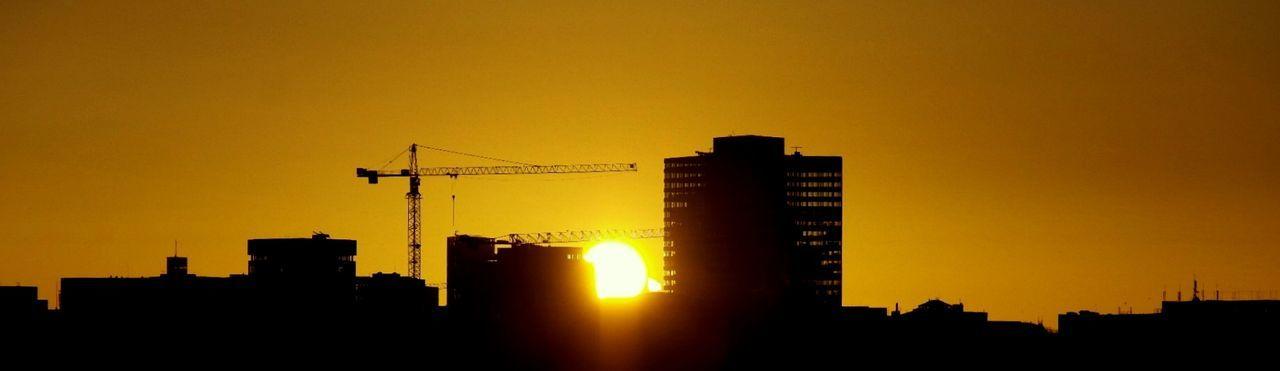 architecture, sunset, silhouette, built structure, building exterior, orange color, development, construction site, city, no people, crane, outdoors, illuminated, skyscraper, sky