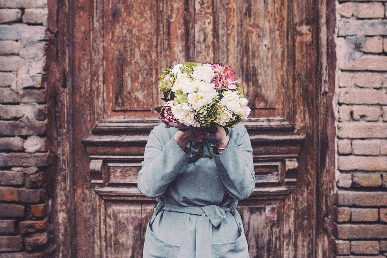 Woman With Face Covered By Flowers Against Wooden Door