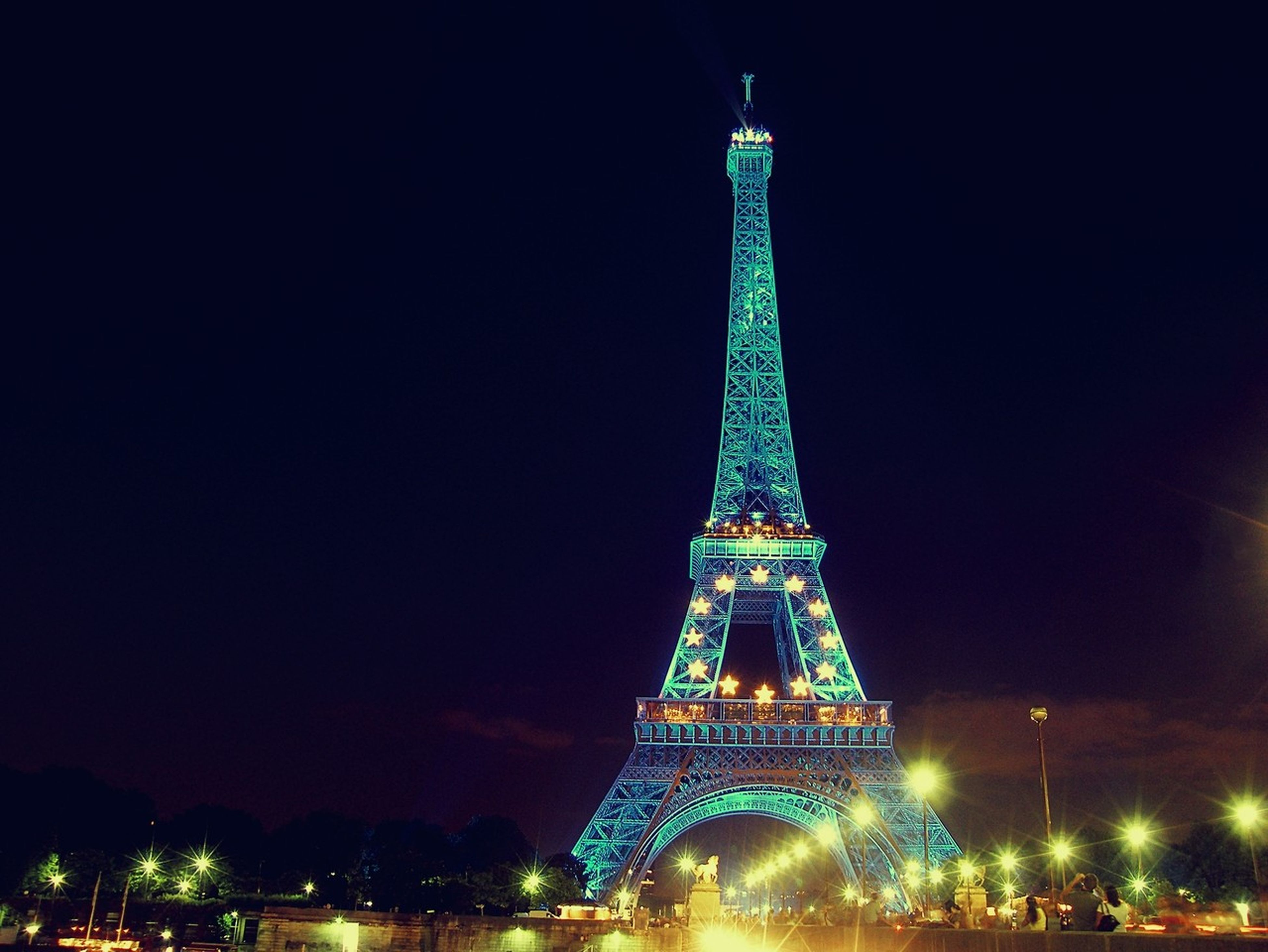 illuminated, night, architecture, famous place, built structure, travel destinations, international landmark, tourism, capital cities, travel, city, eiffel tower, building exterior, low angle view, tower, sky, long exposure, tall - high, clear sky, bridge - man made structure
