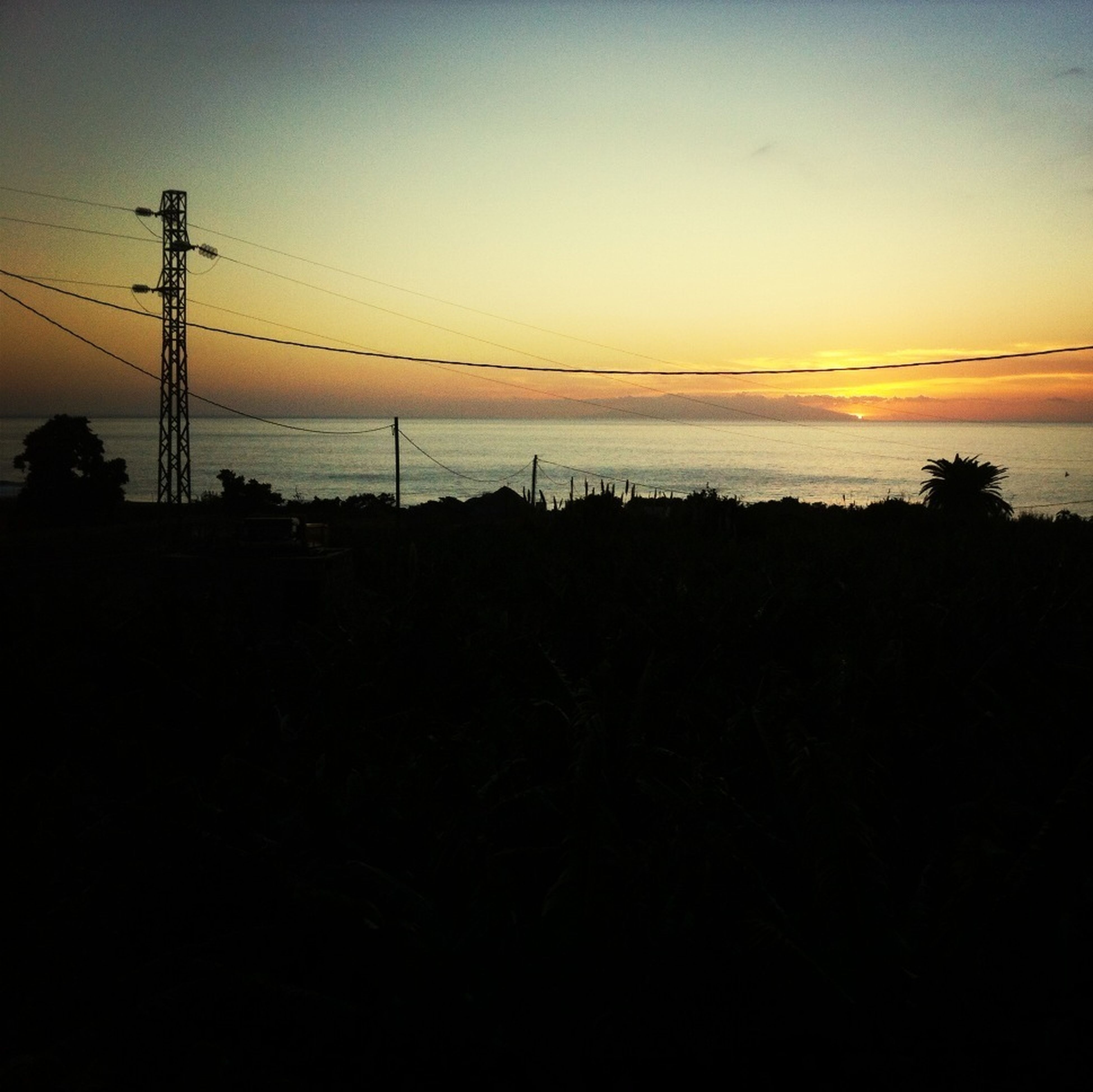 sunset, silhouette, power line, electricity pylon, sky, electricity, power supply, connection, orange color, cable, tranquil scene, water, scenics, tranquility, beauty in nature, nature, dusk, clear sky, outdoors, idyllic