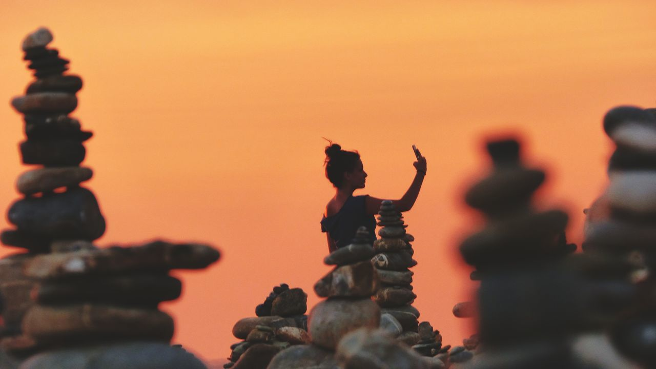 EyeEm Selects Close-up Sunset_collection Sunset Silhouettes Orange Color Orange Sky Sunset Sky Zen Rock At Sunset Zen Rock On Beach Zen Rocks Silhouette Stability Stack In A Row Woman Taking A Selfie Woman Taking Photos On Mobile Milfontes Praia Do Farol Balance Rock Formation Rock - Object