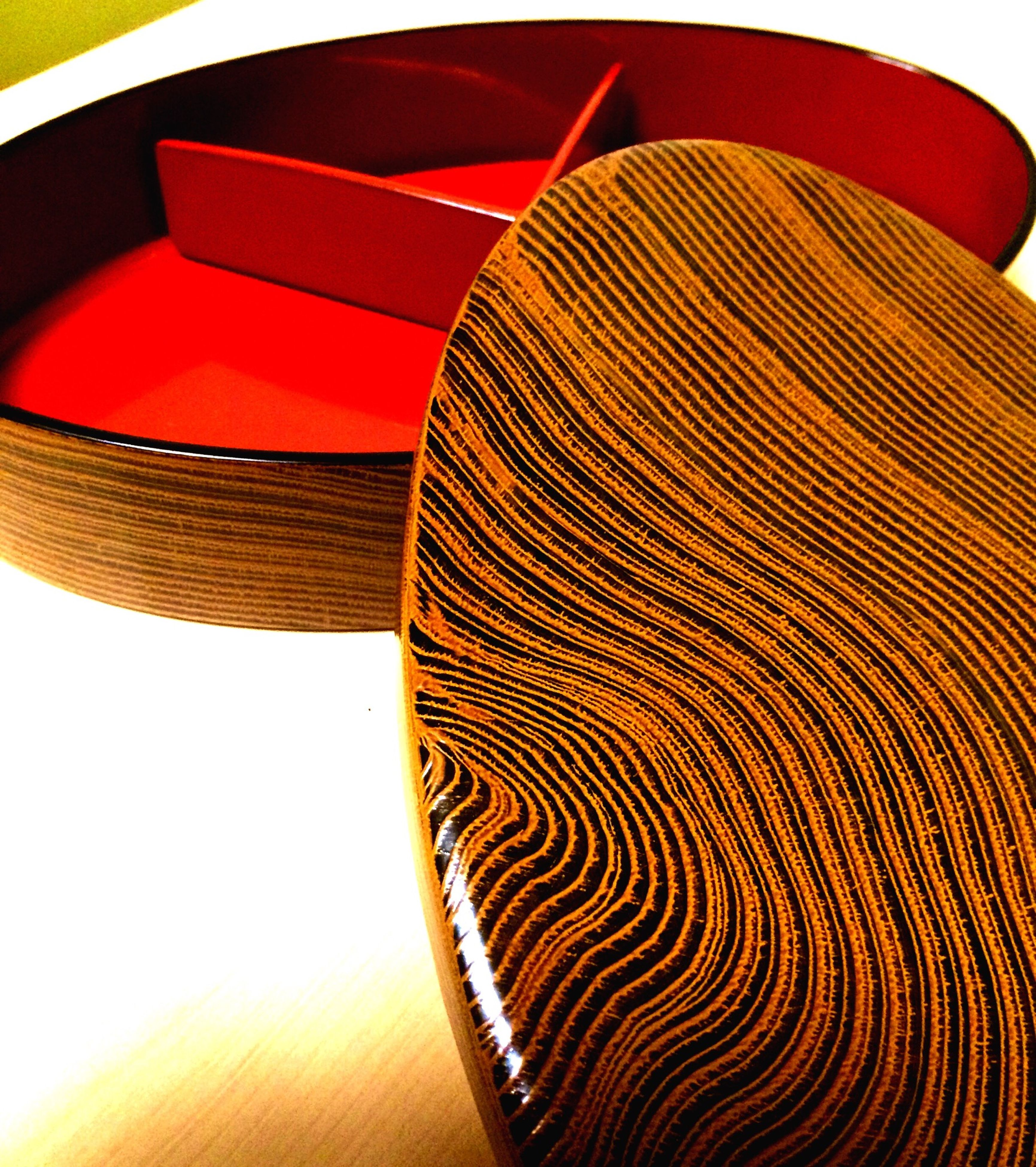 pattern, spiral, indoors, close-up, red, single object, striped, circle, no people, design, part of, wood - material, still life, orange color, shape, sunlight, wicker, arts culture and entertainment, geometric shape, day