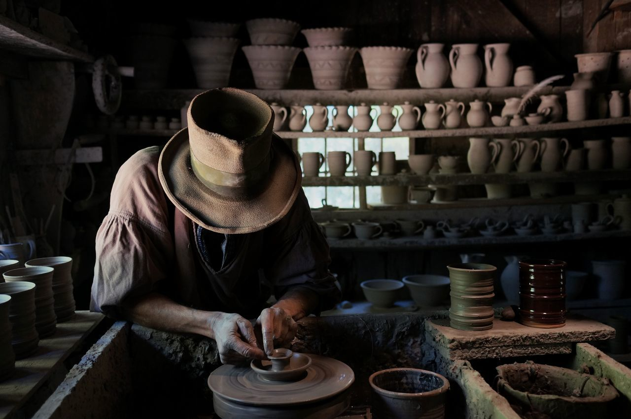 the potter. Old-fashioned Real People One Person Indoors  Craft Craftmanship Pottery Traditional Traditional Craft Handmade Made By Hand Working Hands Hunched
