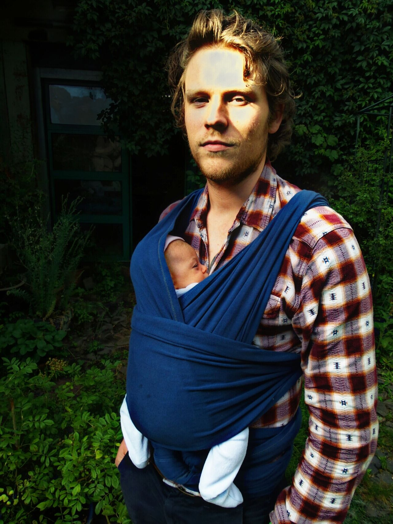 Daddy Cool  No Smile Young Father With Babygirl In A Sling Standing In The Garden Green Plants In The Background Portrait Of A Young Man Baby's First Days In The Backyard Langenselbold Germany🇩🇪 My New Family Fatherhood Moments
