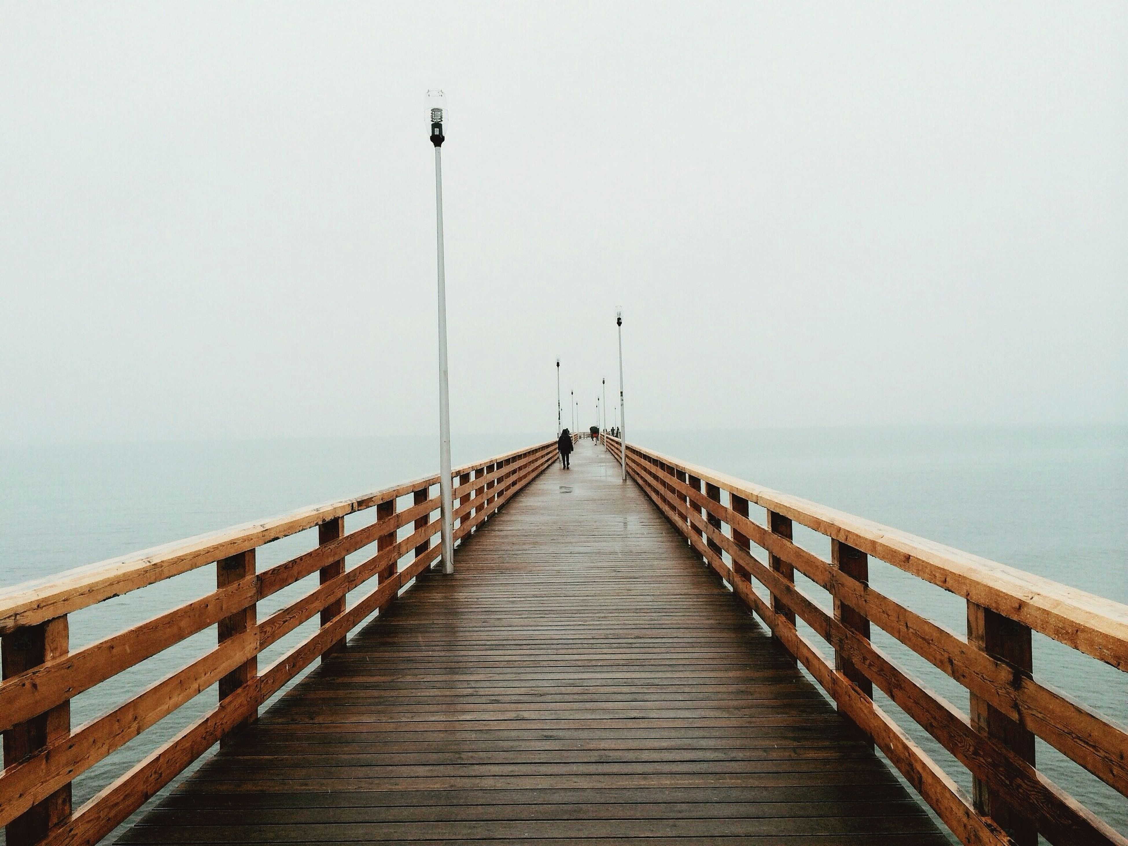 the way forward, sea, pier, railing, water, horizon over water, diminishing perspective, clear sky, copy space, tranquility, tranquil scene, long, vanishing point, wood - material, boardwalk, jetty, built structure, scenics, street light, nature