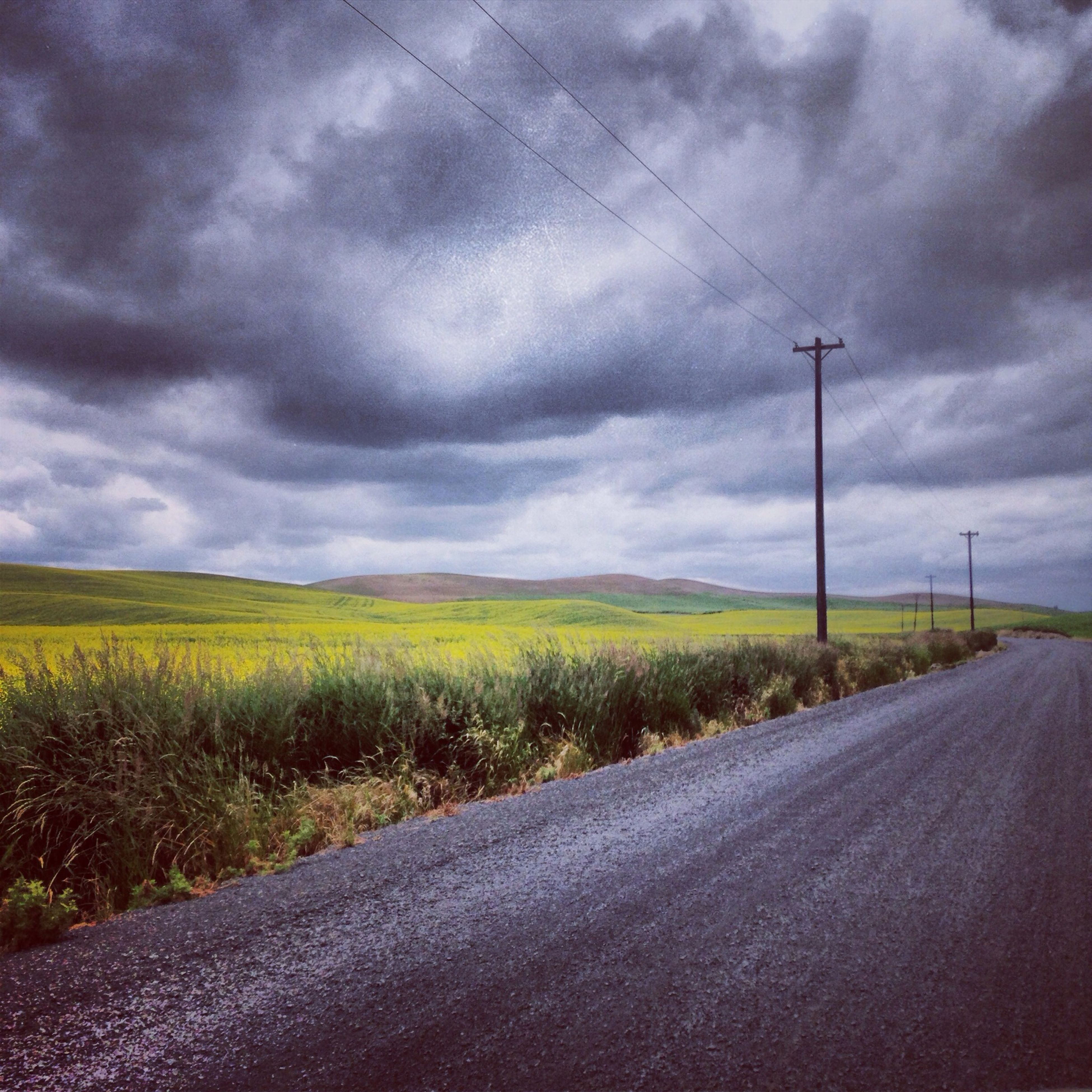 sky, road, the way forward, cloud - sky, transportation, cloudy, landscape, diminishing perspective, field, country road, road marking, cloud, tranquil scene, tranquility, vanishing point, nature, rural scene, grass, scenics, street