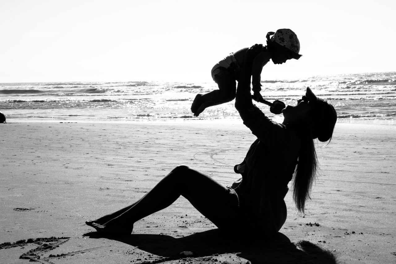 Silhouette Mother Playing With Baby At Beach Against Sky