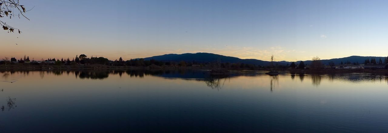 reflection, water, sunset, tranquil scene, nature, beauty in nature, no people, scenics, tranquility, waterfront, lake, sky, clear sky, outdoors, mountain, silhouette, building exterior, architecture, day