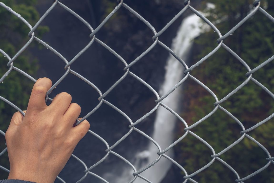 Safety first Protection Security Safety First Safety Metal Outdoors Human Hand Chainlink Fence Chainlink Danger Fence Adults Only Close-up Keep Out Waterfall Staying Safe Safe Woman Focus On Foreground Concept Conceptual