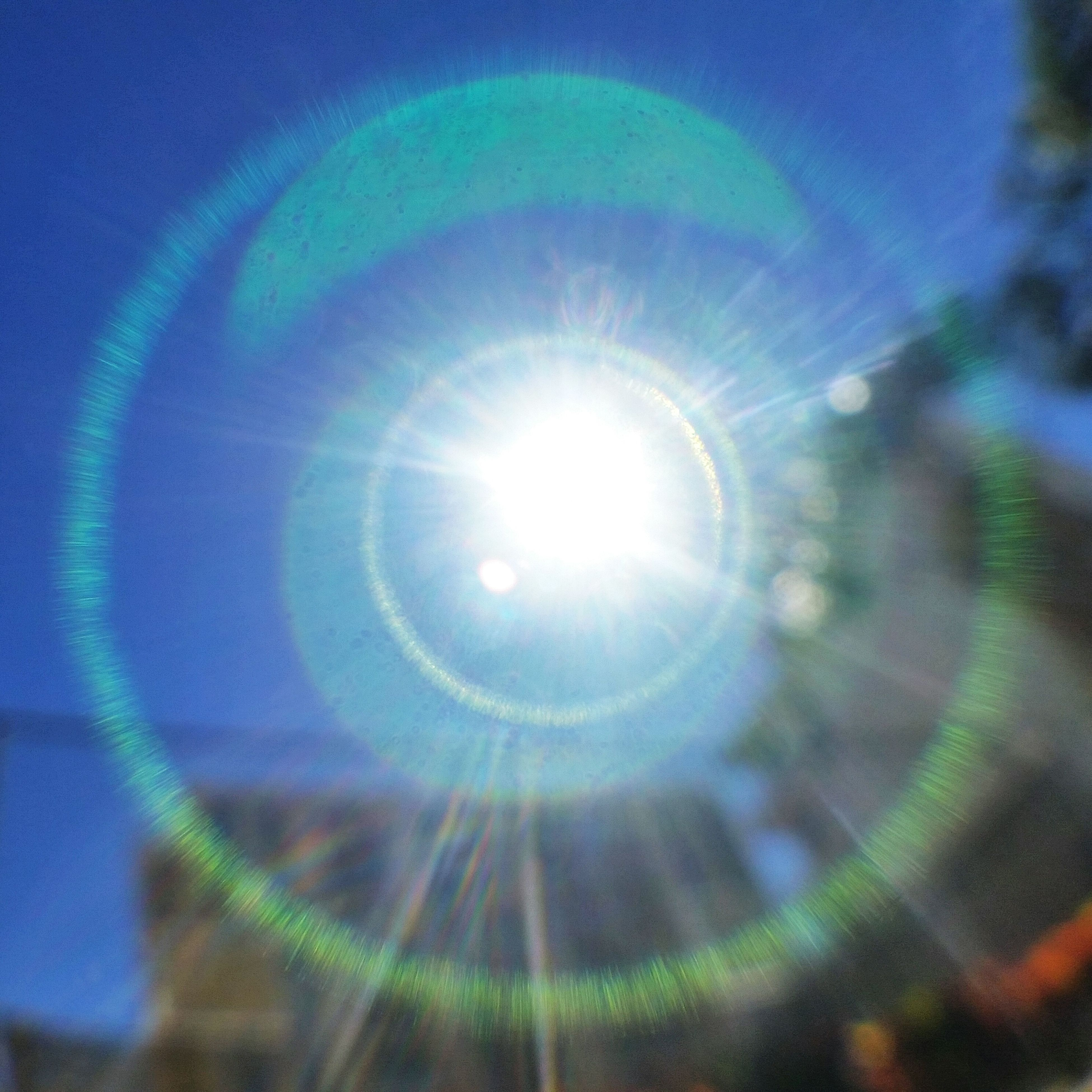 low angle view, lens flare, illuminated, circle, glowing, pattern, sun, blue, geometric shape, sky, lighting equipment, no people, bright, shiny, outdoors, night, sunbeam, backgrounds, light - natural phenomenon, sphere