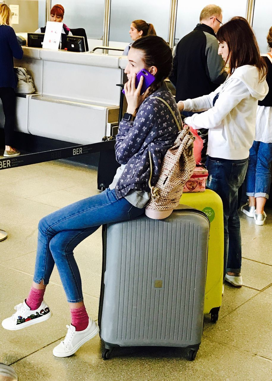 full length, sitting, casual clothing, real people, indoors, young women, young adult, luggage, day, one person, adult, people
