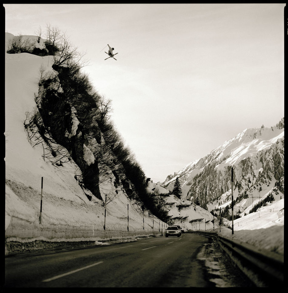Skier jumping over a road at St Christoph am Arlberg in Austria. Hasselblad Action Skiing Ski Capture The Moment Daredevil Mountains Mountain Alps Blackandwhite