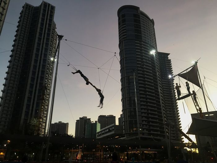 A trapeze instructor and a student practise during a training session at the Flying Trapeze Philippines in Bonifacio Global City, in Taguig, Metro Manila. Building Exterior Architecture Built Structure City Skyscraper Low Angle View Outdoors City Life Sky Cityscape Sunset Silhouettes Philippines Manila Silhouette Adventure Flying Trapeze Flying High Trapeze Flyingtrapeze Aerobatics