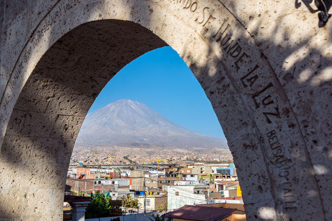 Looking at El Misti Volcano through and arch towering over Arequipa, Peru America Andes Andesmountains Architecture Arequipa Blue Built Structure City City Cityscape Cityscape El Misti History Landmark Misty Nature Outdoors Peru Peruvian Sky South Stratovolcano Tourism Travel Destinations Volcano