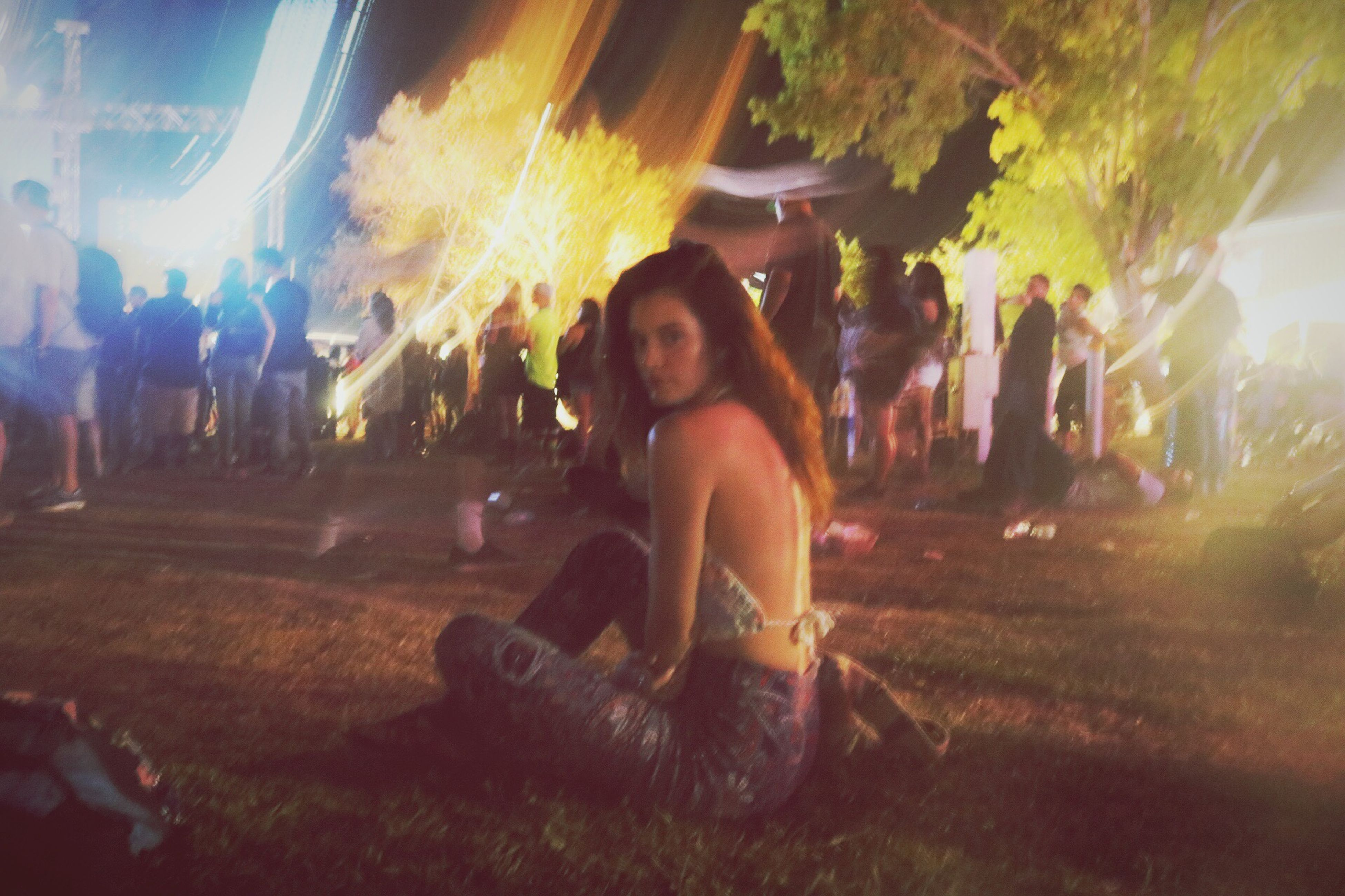 lifestyles, leisure activity, night, enjoyment, illuminated, sunbeam, lens flare, fun, medium group of people, casual clothing, crowd, outdoors, glowing, mixed age range, smoke - physical structure