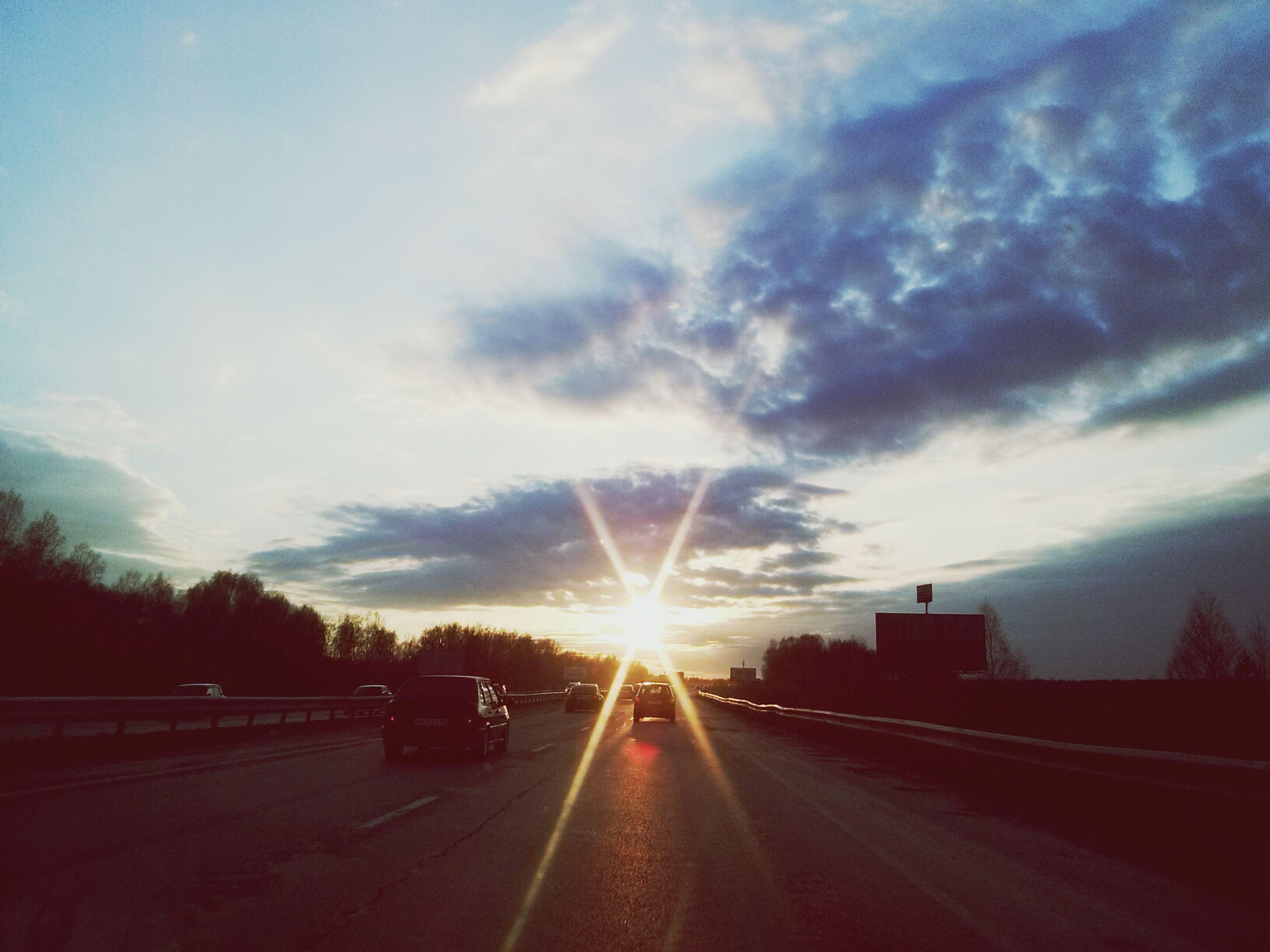 sunset, sun, sky, road, transportation, the way forward, sunbeam, cloud - sky, sunlight, diminishing perspective, vanishing point, lens flare, street, car, road marking, cloud, silhouette, nature, cloudy, outdoors