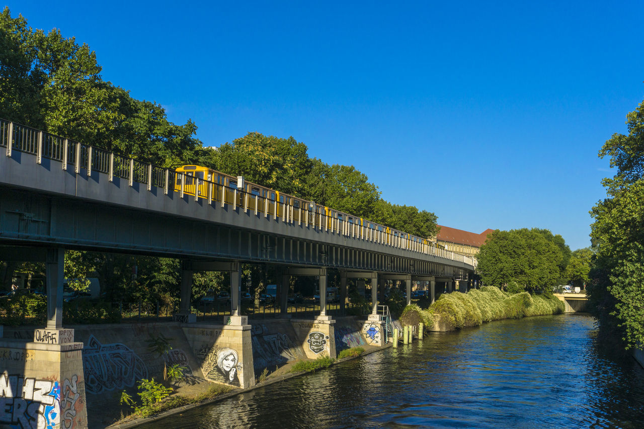 bridge - man made structure, connection, architecture, built structure, tree, transportation, day, blue, river, outdoors, covered bridge, water, no people, bridge, sky, nature, building exterior, clear sky